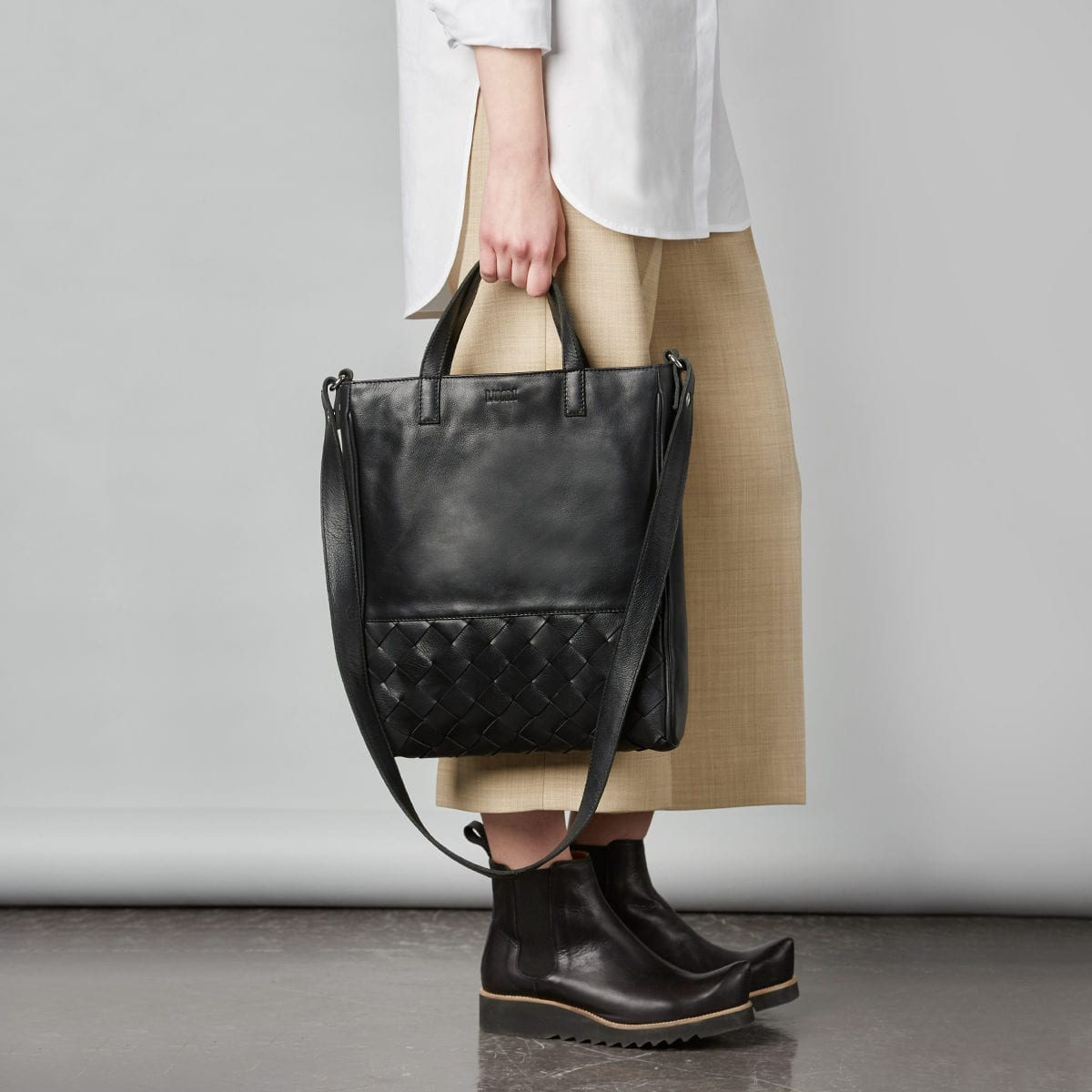 LUMI Signe Woven Tote in classic black. This minimalistic tote bag with woven textured details ticks all the boxes for a perfect day bag. Signe Tote fits a 13″ laptop and the light padding keeps it safe